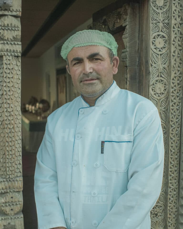 A local male restaurant owner in a cook's coat and hairnet in front of a wooden doorway in Passu, Gilgit-Baltistan, Pakistan